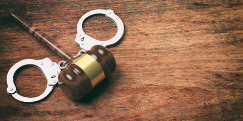 Metal handcuffs and judge gavel isolated on wooden background, copy space, 3d illustration