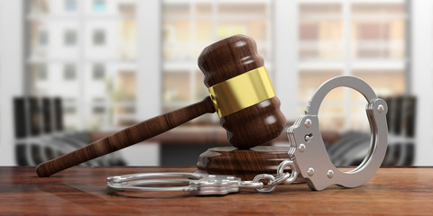 Metal handcuffs and judge gavel on wooden desk, blur office background. 3d illustration