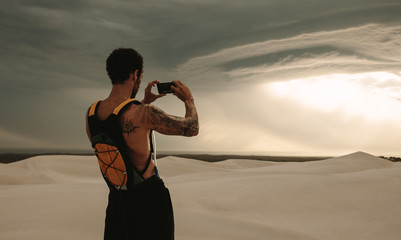 Fit man taking pictures of cloudy sky in desert