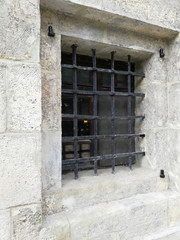 The windows in the concrete wall are covered with bars.