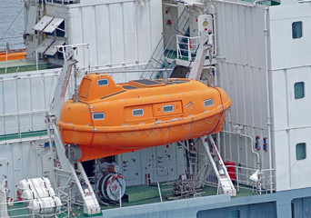 orange lifeboat on ship