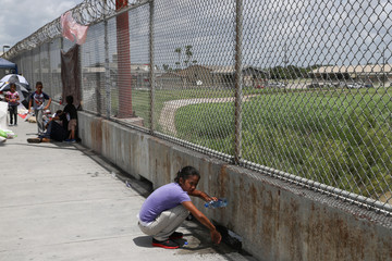 A Honduran girl bathes with a water bottle on the Mexican side of the Brownsville-Matamoros International Bridge after her asylum seeking family was denied entry by U.S. Customs and Border Protection officers near Brownsville