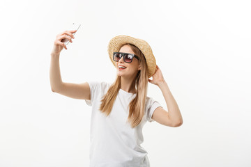 Fashion and Lifestyle Concept: pretty young woman wearing a hat, sunglasses takeing a photo of herself by mobile phone isolated over white background