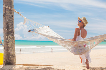 Young woman in white dress and straw hat relaxing in a hammock by the beach