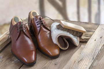 Pair of brown gentleman shoes with shoe maintenance set on old wooden table