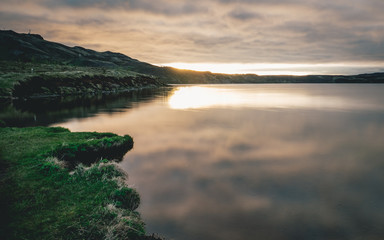 lake in iceland with sunset and reflection of water