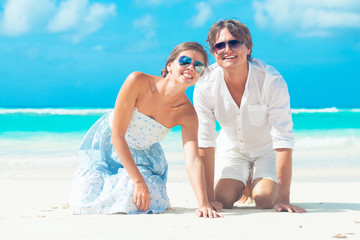portrait of happy young couple in white on the beach