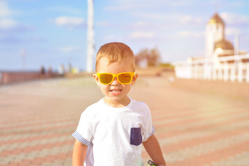 Portrait of 2 year old boy in bright orange sunglasses that walks along the seaport of Ukraine in Odessa