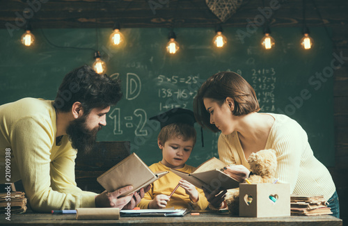 homeschooling concept father and mother reading books teaching