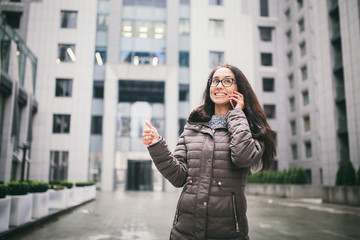 Theme is the business situation. Beautiful young woman of European ethnicity with long brunette hair wearing glasses and coat stands on background of business center and uses phone in hand near ear