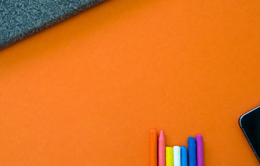 Wall Mural - Notebook with crayon and smartphone on orange background copyspace