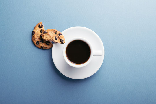 A cup of coffee and american cookies with chocolate chips on blue grey background. Top view.