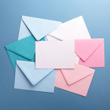 Group of colorful envelopes on grey table with empty card. Correspondence concept. Mockup.