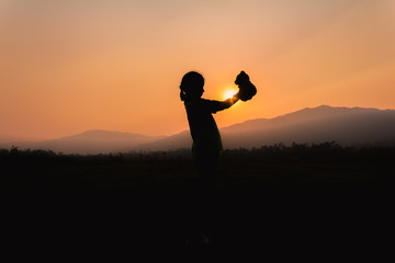 Silhouette little girl playing teddy bear at a sunset time