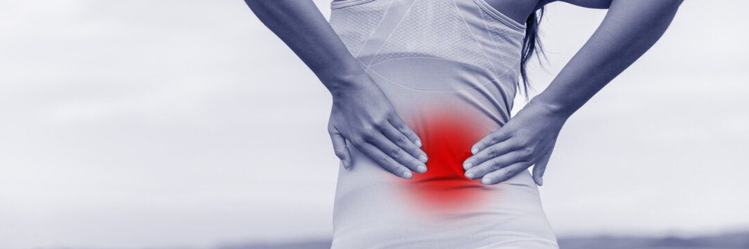 Back pain - woman having painful muscle injury in lower back. Fitness girl sport girl with sports injury outdoor. Blue filter with red zone circle showing the painful area.
