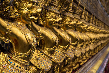 Row of golden Garuda figures from Thai mythology, adorning the interior of Wat Phra Kaew (Temple of the Emerald Buddha). Located in the Grand Palace, Bangkok, Thailand.