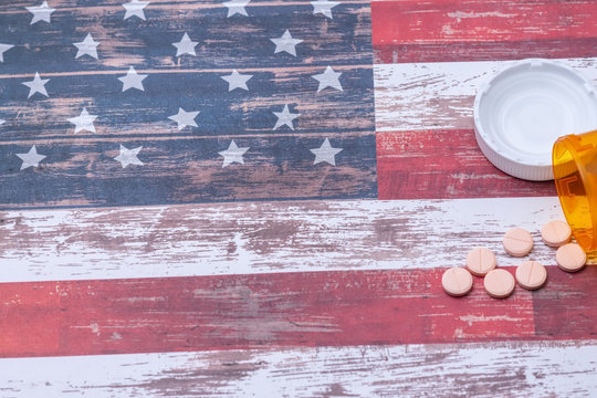 Bottle of pills spill on American flag with room for text