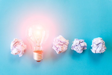 Inspiration and great idea concept. light bulb with crumpled colorful paper on blue background.