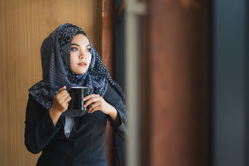 asian muslim woman enjoying a cup of coffee
