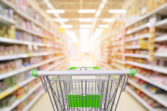 Supermarket aisle product shelves interior blur background with empty shopping cart