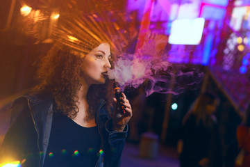 Young attractive red-haired girl smokes electronic cigarette. She walks down street. Evening city lights and signs flashing. Alternative to cigarette smoking