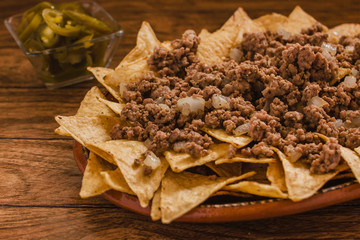 nacho chips corn garnished with ground beef, melted cheese in plate on wooden table mexican spicy food in mexico