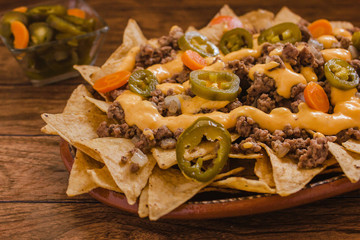 nacho chips corn garnished with ground beef, melted cheese, jalapeños peppers in plate on wooden table mexican spicy food in mexico