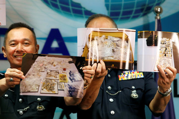 Police officers display photos of items from a raid during a news conference in Kuala Lumpur,