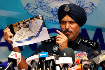 Amar Singh, head of Malaysia's Commercial Crime Investigation Department (CCID), displays a photo of items from a raid during a news conference in Kuala Lumpur