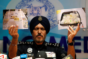 Amar Singh, head of Malaysia's Commercial Crime Investigation Department (CCID), displays photos of items from a raid during a news conference in Kuala Lumpur