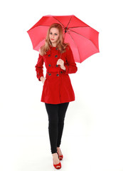 portrait of pretty blonde girl wearing red trench coat, holding an umbrella. full length standing pose. isolated on white studio background.