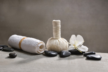 Wall Murals Spa pile of black stones and white orchid, herbal ball.towel on gray background
