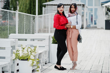 Two fashionable arabian girls friends posed outdoor. Stylish muslim womans.