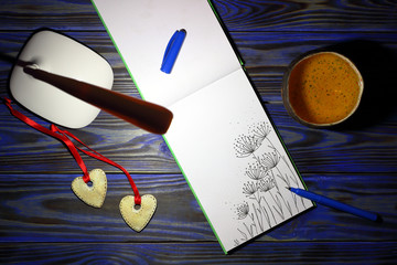 White table lamp, sheet of open notepad with a picture of leaves of plants in doodling style, pen, cup of tea, two decorative hearts on blue wooden background at night. Top view