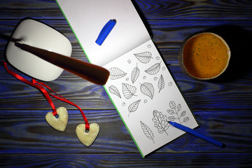 White table lamp, sheet of open notepad with a picture of leaves of plants in doodling style, pen, cup of tea, two decorative hearts on blue wooden background at night. Top view.