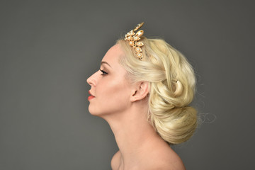 portrait of blonde woman wearing golden crown, grey studio background.