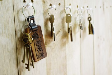 House key with wooden home keyring hanging on wood board background, property concept, copy space