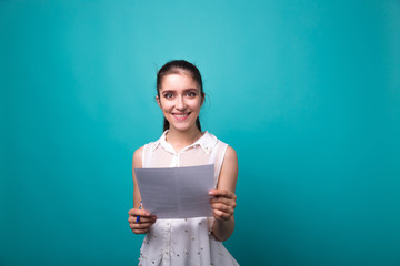 girl with a paper in hands on studio cyan blue background