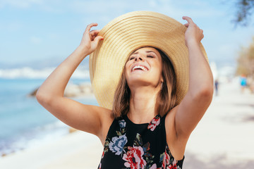 Laughing carefree young woman at the beach