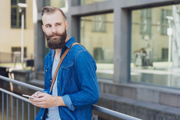 Casual young bearded man standing watching