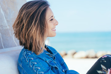 Smiling young woman relaxing overlooking a beach