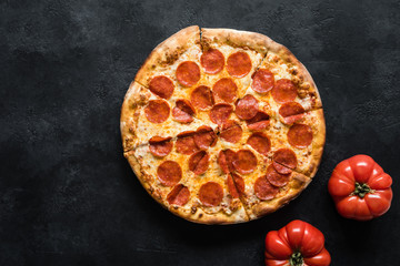 Pepperoni pizza on black concrete background. American pepperoni pizza, top view