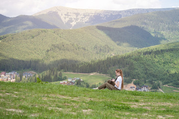 Girl with the camera sits on a hill and viewing photos. Mountains in the background