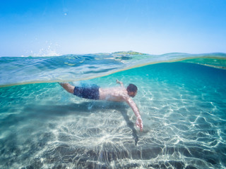 Young caucasian man diving in turquoise sea. Sardinia sea. Half underwater photography