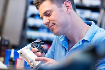 Male Apprentice Measuring Component In Factory