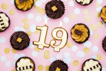 Number 19 gold candle with cupcakes against a pastel pink background
