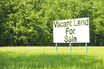 Advertising billboard immersed in a rural scene with Vacant Land for Sale written on it - image with copy space
