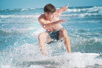 Skimboarding young man ocean