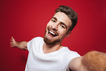Portrait of a smiling young bearded man taking a selfie