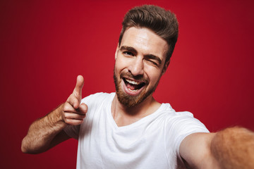 Portrait of a cheerful young bearded man pointing finger